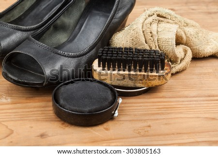Shoe polish with brush, cloth and worn ladies court shoe on wooden platform. - stock photo