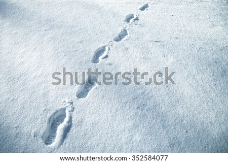Shoe prints in fresh snow on snowy meadow. Blue color filter used. - stock photo