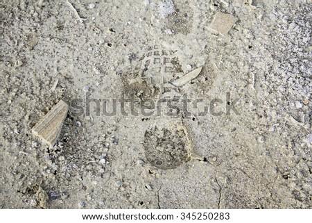 Shoe prints on arid land, hiking and nature - stock photo