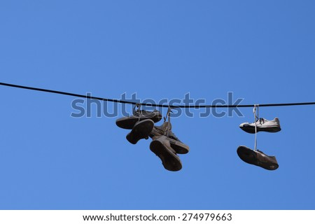 Shoe tossing old sneakers footwear with tied shoelaces hanging from a wire. - stock photo