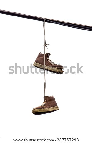 Shoe Tossing, Old Sneakers Hanging on Power line Wire, Isolated on White Background - stock photo