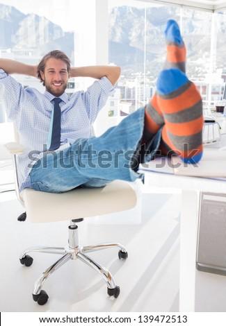 Shoeless designer kicking back at his desk and smiling - stock photo