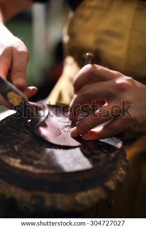 Shoemaker performs shoes in the studio craft - stock photo