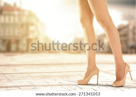 shoes and woman legs in city and sunset  - stock photo