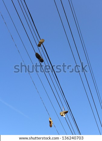 Shoes hanging from power lines are said to be gang symbols or the stuff of urban legends - stock photo