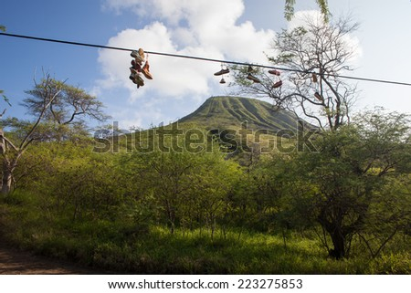 Shoes Hanging on a Wire in front of Koko Crater, Oahu - stock photo