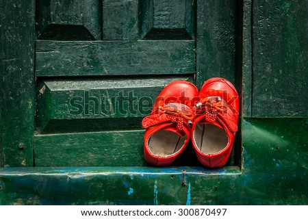 Shoes left at a green door - stock photo