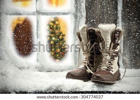 shoes on window sill of snow and xmas tree in home space  - stock photo