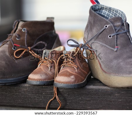 Shoes tied together mom and dad's son. The symbol of family love - stock photo