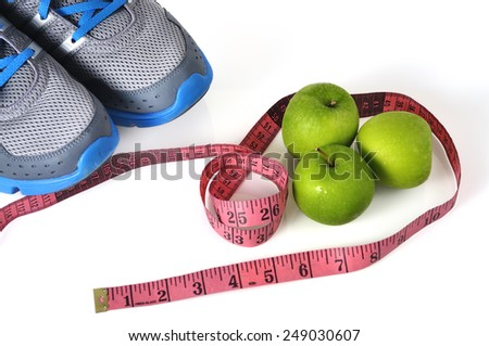 Shoes with Green Apple and Measure Tape on White Background, Healthy Lifestyle Concept and Selective Focus - stock photo