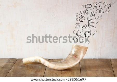 shofar (horn) on wooden table with set of infographics over textured background. rosh hashanah (jewish holiday) concept . traditional holiday symbol.  - stock photo