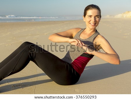 Shoot of a beautiful woman working her ABS in the beach - stock photo