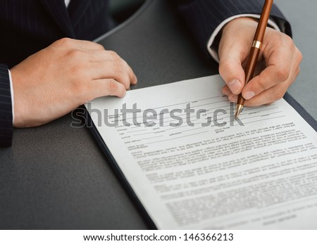 Shoot of financial director's hands signing business contract at the desk in his office. - stock photo