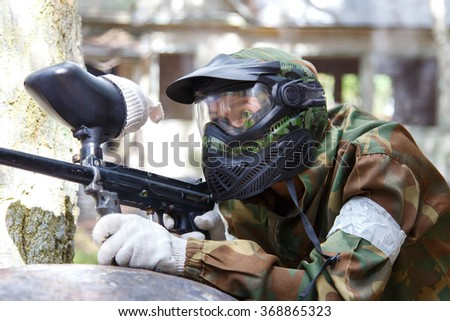 Shooter in paintball mask - stock photo