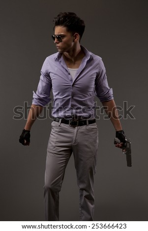 shooter or contractor on grey background with handgun looking determined - stock photo