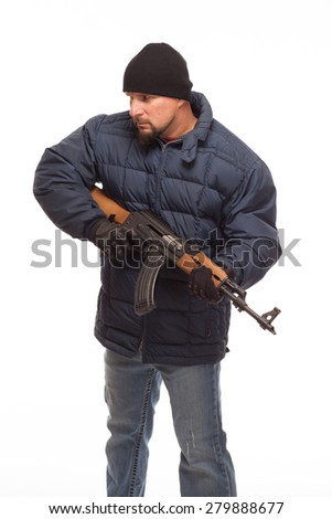 Shooter with AK 47 and cold weather gear looking off to the side on white background. - stock photo