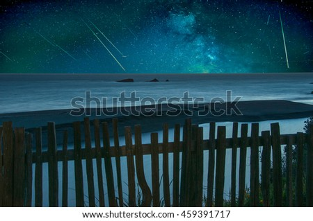 Shooting stars falling over a tranquil ocean panorama. - stock photo
