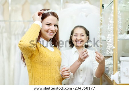 Shop assistant  helps the bride in choosing bridal diadem at shop of wedding fashion. Focus on girl - stock photo