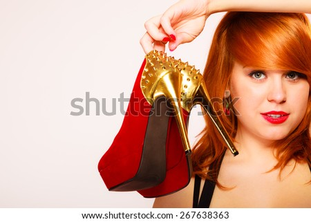 Shopaholic, fashion and women style. Shopping time. Young red haired female holding high heeled shoes in hands on pink background. Studio shot. - stock photo