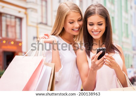 Shopaholic friends. Two attractive young women holding shopping bags and looking at mobile phone together while standing outdoors - stock photo
