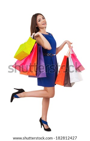 Shopaholic girl. Full length of beautiful young woman in blue dress holding shopping bags and smiling at camera - stock photo