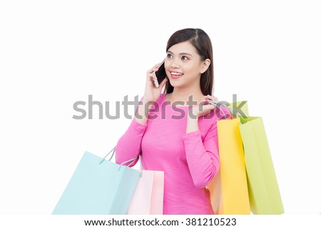 Shopaholic woman. Attractive young asian women holding shopping bags and using mobile phone, isolated over white background - stock photo