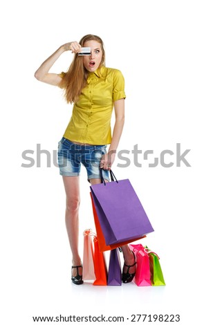 Shopaholic woman with shopping bags and credit card over white background - stock photo