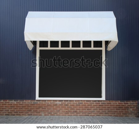 Shopfront vintage store front with canvas awnings and blank display - stock photo
