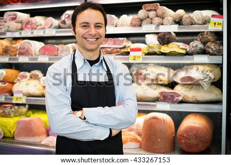 Shopkeeper at work in his grocery store - stock photo