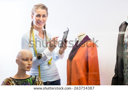 Shopkeeper decorating shop window with new clothes  - stock photo