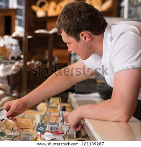 Shopkeeper working in a cheese glass case in a grocery store - stock photo