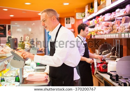 Shopkeepers working in their grocery store - stock photo