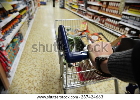 Shopper Pushes a Cart in Supermarket Aisle - Image Has a Shallow Depth of Field - stock photo