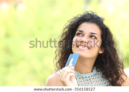 Shopper with a credit card thinking what to buy outdoors with a green background - stock photo