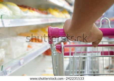 shopper with trolley at supermarket - stock photo