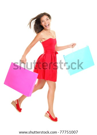 Shopper - woman shopping holding shopping bags in red summer dress. Young asian woman walking cheerful and smiling isolated in full body on white background. Mixed race Asian / Caucasian female model. - stock photo