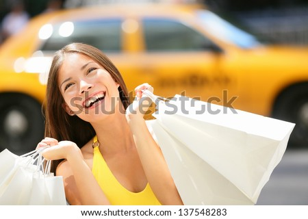 Shopper woman shopping in New York City, Manhattan, USA. Shopper girl holding shopping bags smiling happy with yellow taxi cab in background. Young multiracial Asian Caucasian female model in dress. - stock photo