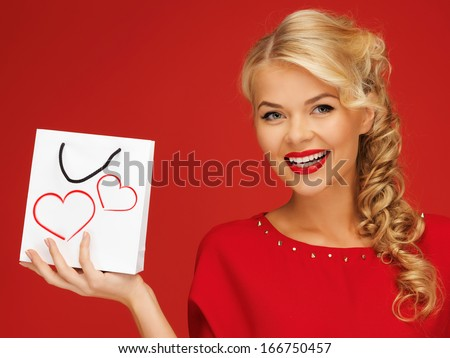 shopping and love concept - lovely woman in red dress with shopping bag - stock photo
