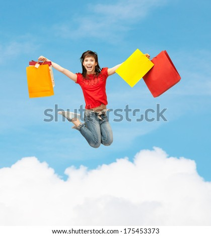 shopping and motion concept - happy girl with shopping bags - stock photo