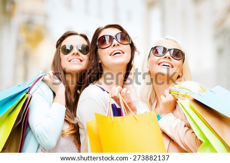shopping and tourism concept - beautiful girls with shopping bags in ctiy - stock photo