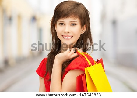 shopping and tourism concept - beautiful woman with shopping bags in ctiy - stock photo