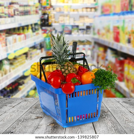 Shopping basket with groceries  on shop of background - stock photo