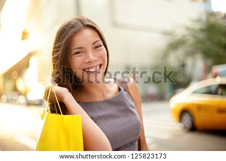 Shopping business woman on Manhattan, New York City. Fresh blissful mixed race Asian / Caucasian young professional  holding shopping bags outdoors in streets of New York - stock photo