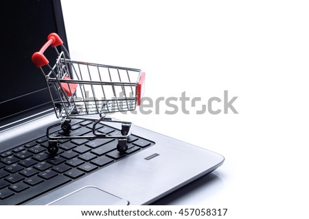 Shopping cart and laptop over white background, business conceptual - stock photo