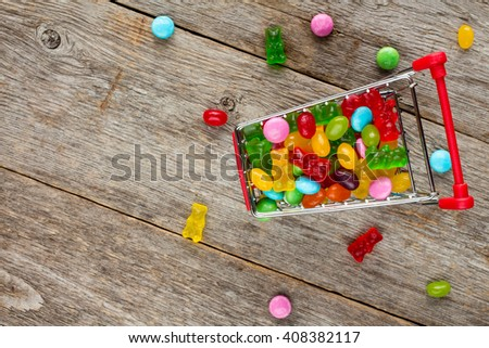 Shopping cart full of candies on a wooden background - stock photo