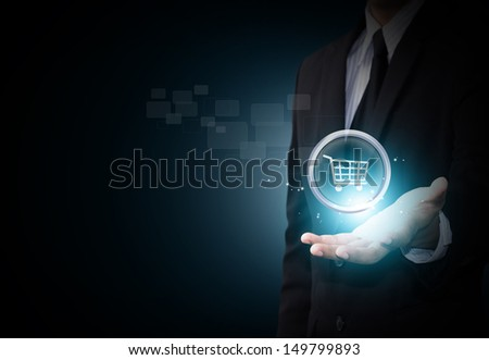 Shopping cart icon in business hand - stock photo