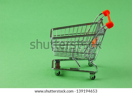 Shopping cart on the green background - stock photo