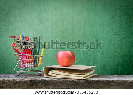 Shopping cart, school supplies, stationery, notebook, apple on dark wood top and grunge green chalkboard background w/ empty blank copy space for adding text message / announcement/ advertisement - stock photo