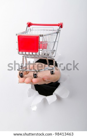 Shopping cart through hole in paper - stock photo