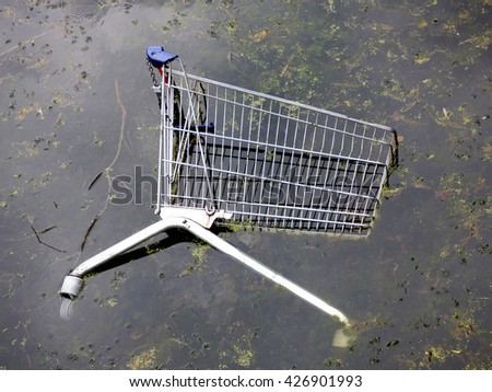 shopping cart thrown in the water - stock photo